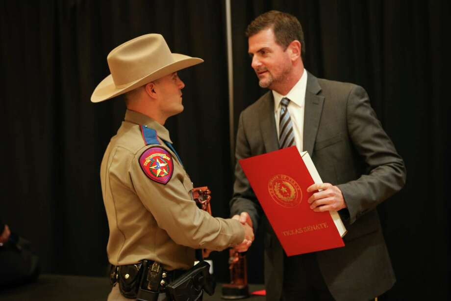 Texas Department of Safety Trooper Benjamin Polansky, left, shakes hands with state Sen. Brandon Creighton, R-Conroe, after receiving an Officer of the Year award during the East Montgomery County Improvement District Law Enforcement Appreciation Dinner on Monday, Feb. 26, 2018, at the EMCID Complex in New Caney. Photo: Michael Minasi, Staff Photographer / © 2017 Houston Chronicle