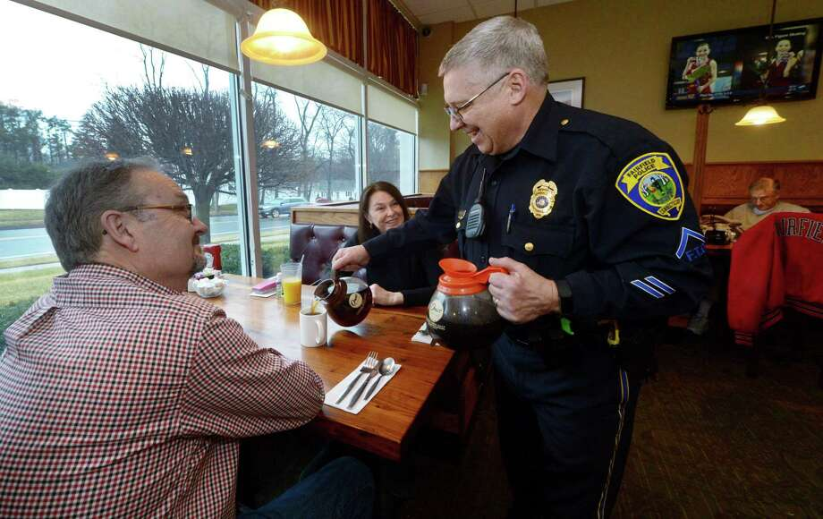 Fairfield police Field Training Officer Anthony Kushinski pours coffee for Doug and Judy Dice during the Tip-A-Cop event Feb. 23 at Chip's Diner in Fairfield. Photo: Erik Trautmann / Hearst Connecticut Media / Norwalk Hour