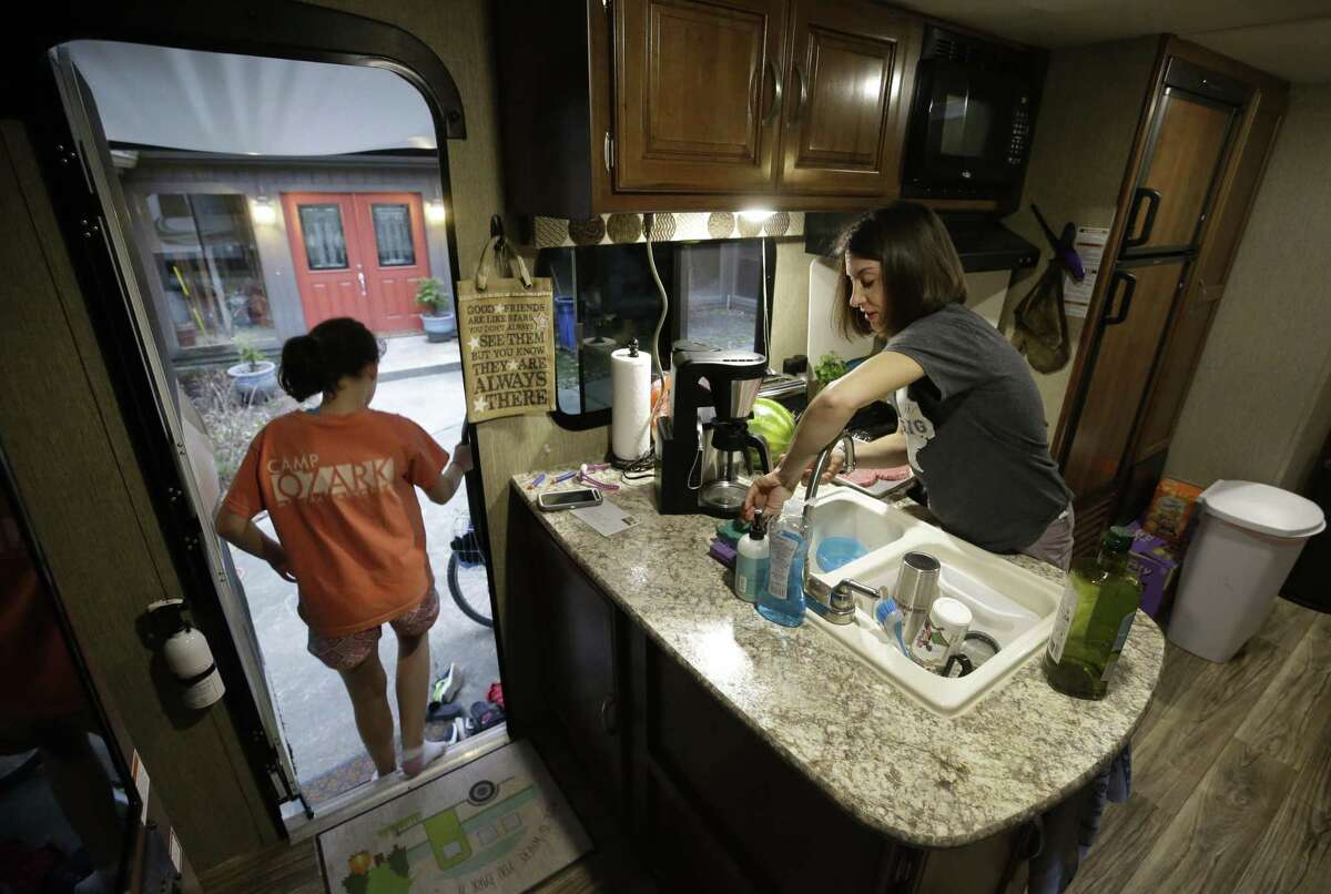 Jennifer Coulter prepares dinner as her daughter, Luke Coulter, 9, left, Chloe Coulter, 11, steps out of the travel trailer parked outside their flooded Kingwood home Wednesday, Feb. 28, 2018. They are living in the travel trailer in the driveway of their home while waiting for their house to be rebuilt after flooding from Hurricane Harvey.