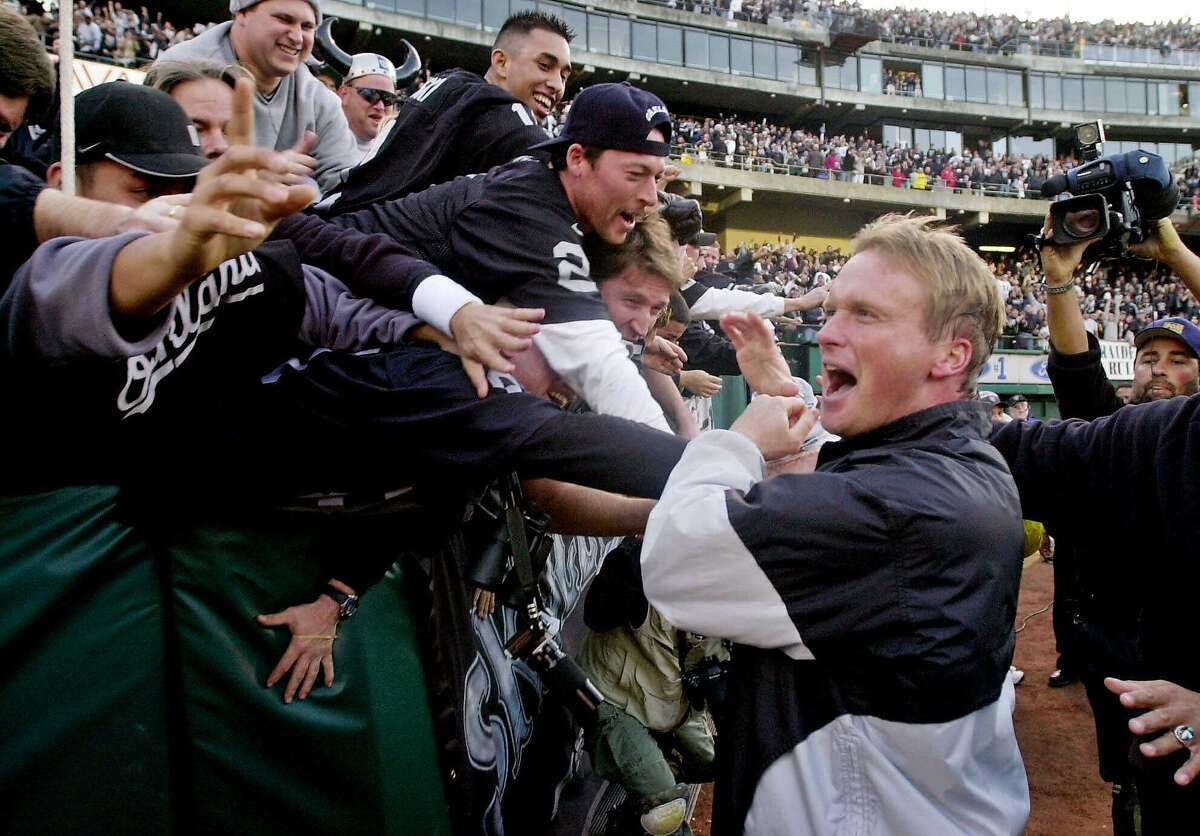 FILE--Oakland Raiders coach Jon Gruden shakes hands with fans after the Raiders defeated the Carolina Panthers 52-9 to win the AFC West championship, Dec. 24, 2000, in Oakland, Calif. There are a lot of similarities between the men who will coach in the AFC title game Sunday, Jan. 14, 2001 _ Brian Billick's Baltimore Ravens against John Gruden's Raiders. The most obvious: both are disciples of the Bill Walsh school of coaching. (AP Photo/Paul Sakuma)