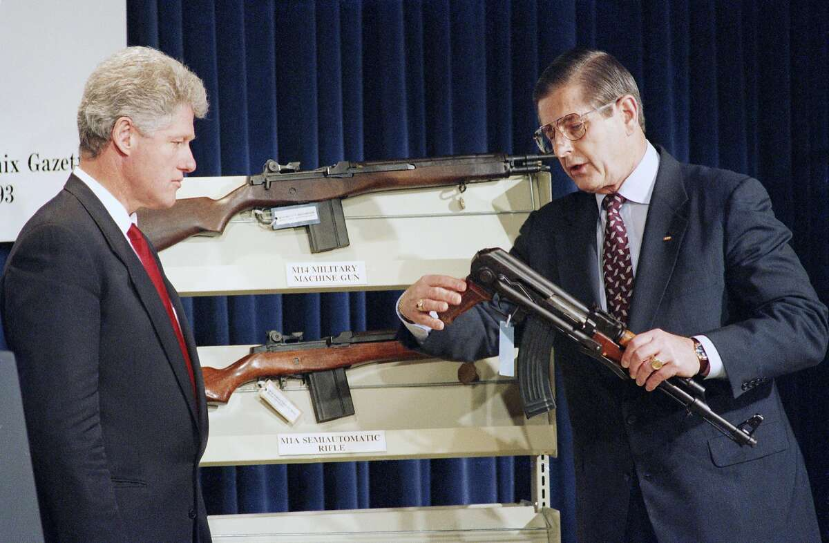 U.S. President Bill Clinton looks on as Bureau of Alcohol, Firearms and Tobacco Director John Magaw holds a AK-47 submachine gun at the White House in Washington on Monday, May 2, 1994 where the President addressed law enforcement officials on banning assault weapons. The AK-47 is not affected by this proposed ban due to being banned by existing legislation. (AP Photo/Dennis Cook)