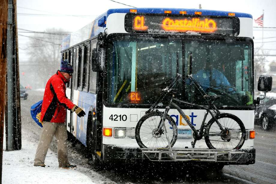 A rider boards a Greater Bridgeport Transit bus as the snow begins to fall along Main Street in Stratford, Conn., Feb. 8th, 2013. Photo: Ned Gerard / Ned Gerard / Connecticut Post