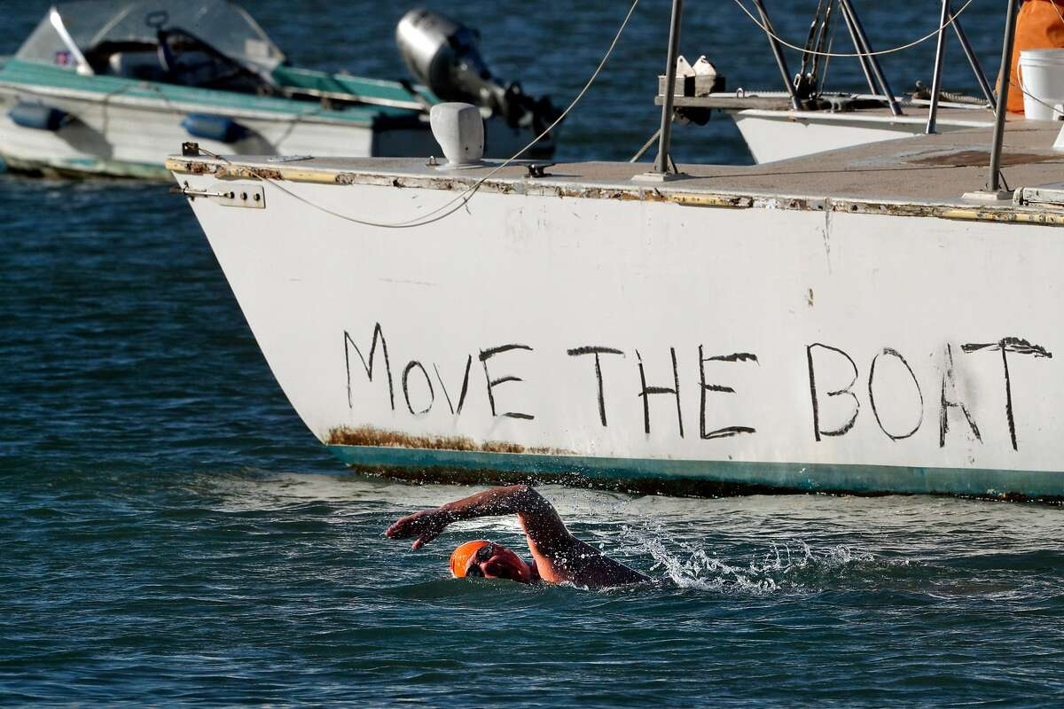 A member of the Dolphin Club swims near a trimaran that is anchored in the water off Aquatic Park in San Francisco, Calif., on Monday, February 26, 2018. For months the trimaran sailboat has been illegally anchored in Aquatic Park by a man identified as Bryan Pennington, who is living aboard. The Dolphin Club has been trying to get rid of him because he is polluting the bay and interfering with their swimming area. The Dolphin Club took the matters to the Presidio police, which has jurisdiction and they had a hearing in federal court.