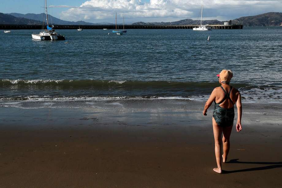 King Sip, a member of the Dolphin Club, walks toward the water for a swim at Aquatic Park where a trimaran sailboat has been illegally anchored for months. Photo: Carlos Avila Gonzalez, The Chronicle