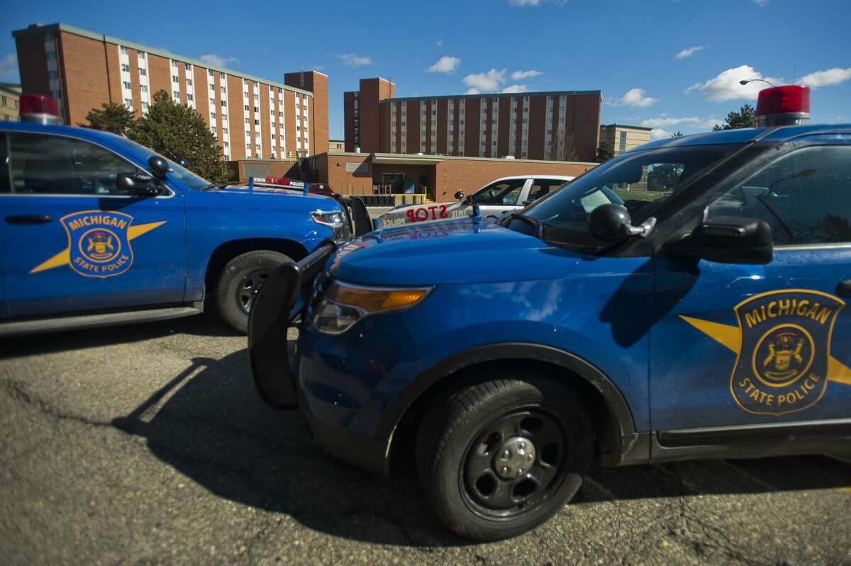 Police vehicles are parked outside of the Towers residence halls as police search for James Eric Davis, Jr., 19, as a person of interest in the shooting deaths of two people at Central Michigan University on Friday, March 2, 2018 in Mt. Pleasant. (Katy Kildee/kkildee@mdn.net)