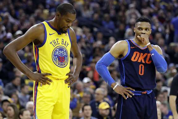 Golden State Warriors' Kevin Durant, left, stands next to Oklahoma City Thunder's Russell Westbrook during the first half of an NBA basketball game Saturday, Feb. 24, 2018, in Oakland, Calif. (AP Photo/Marcio Jose Sanchez)