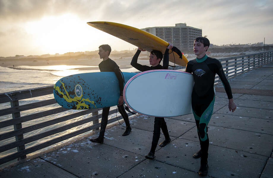 Luke Merritt, 15, from left, Liam Shannon, 14, and Paul Snow, 15, use a fishing pier to walk out to deeper waters to surf in Port Aransas. Photo: Nick Wagner, MBO / Austin American-Statesman