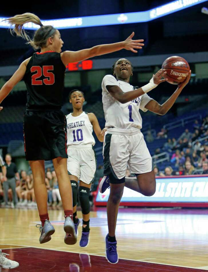 Houston Wheatleys' Telisha Brown (C) drives under Argyles' Sydney Standifer. Argyle vs. Houston Wheatley game in a UIL girls basketball Class 4A state semifinal on Friday, March 2, 2018 at the Alamodome.