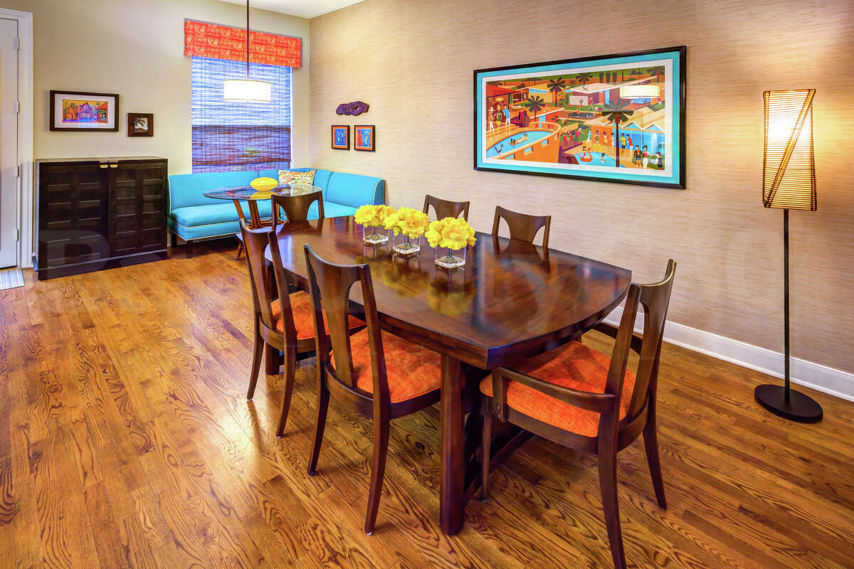 Wood floors and neutral walls provide warmth in this room, but turquoise in the banquette and art and coral/orange in the window treatments and seat cushions add pops of color.