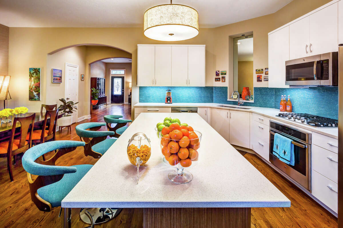 In the same townhome, a bold turquoise tile backsplash in the kitchen is complemented by turquoise upholstered counter chairs and a nearby turquoise banquette. When using a bold accent color, follow the Rule of Three: use it three times in the same room.