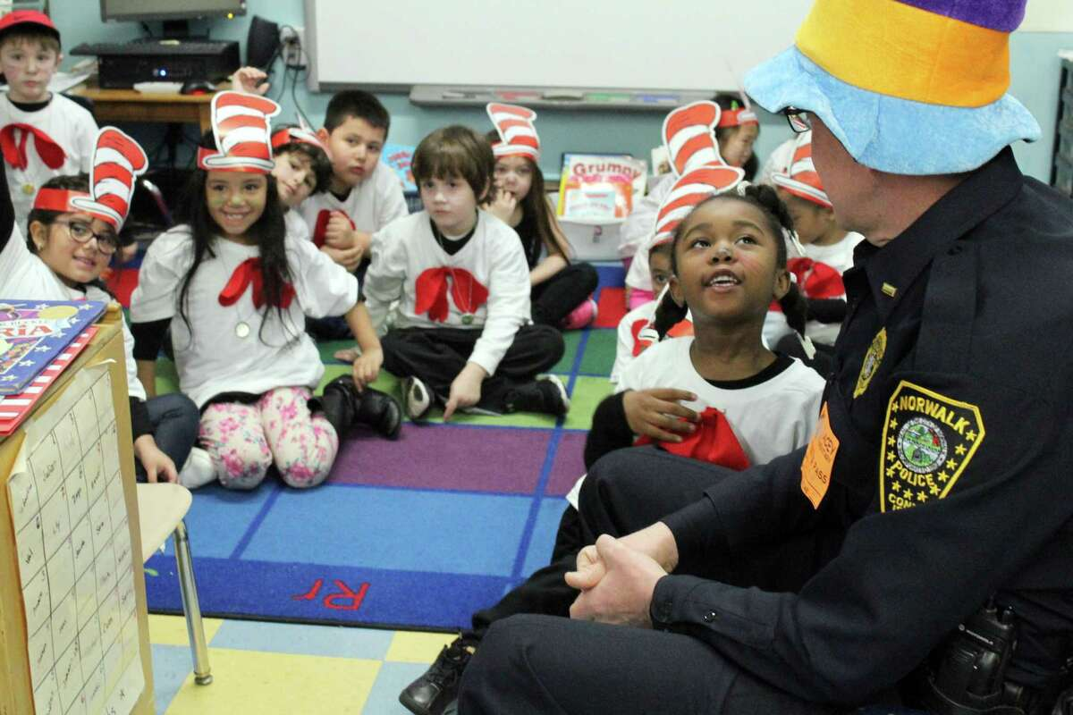 Kindergartener Anna St. Louis asks Norwalk Lt. James Walsh a question during Tracey Elementary School's celebration of National Read Across America Day on Friday, March 2.