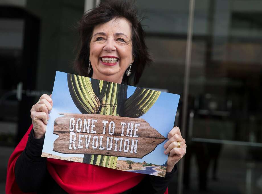RoseAnn DeMoro shows a sign at her retirement party in Oakland. Photo: Jessica Christian, The Chronicle