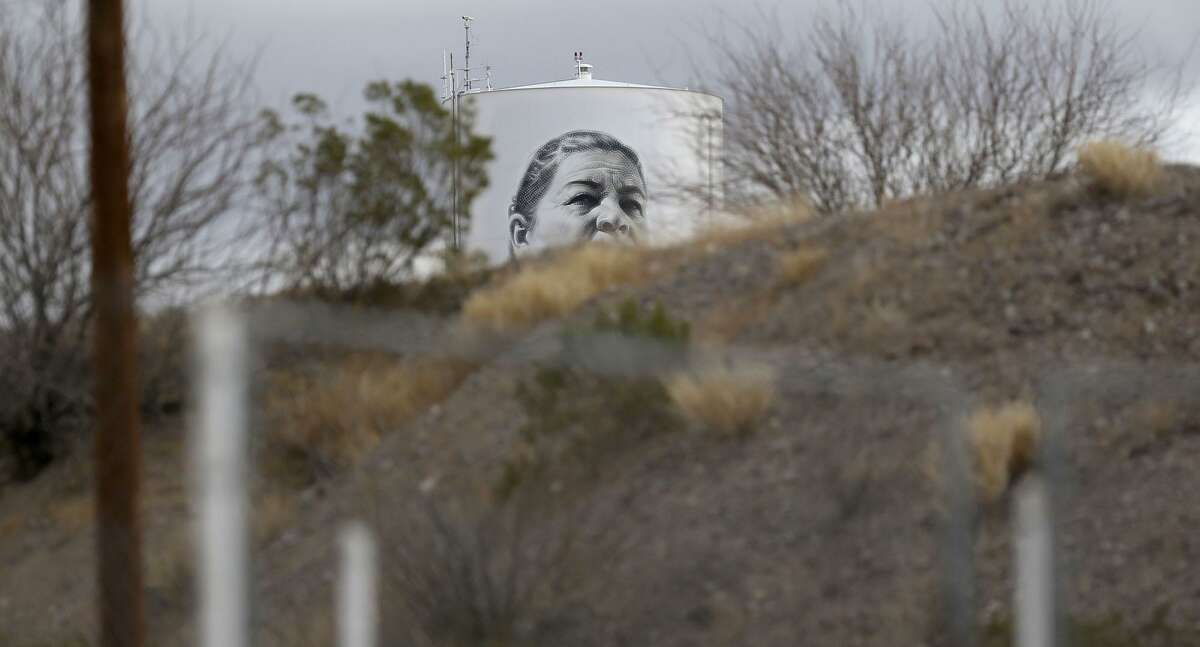 A portrait is visible on a water tower in Presidio, Texas near the Mexican border. The portrait has been painted by artist Miles MacGregor, also known as