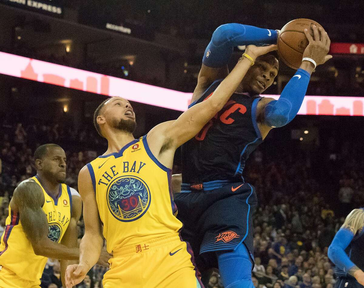 Golden State Warriors guard Stephen Curry (30) is charged with a foul on Oklahoma City Thunder guard Russell Westbrook (0) as they compete for a Warrior rebound on Saturday, Feb. 24, 2018 in Oakland, CA.