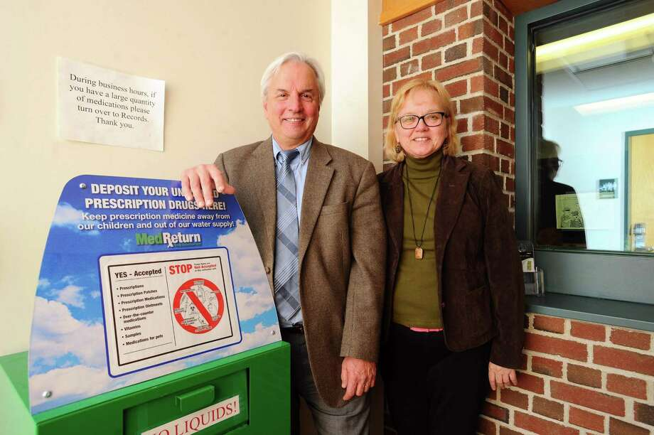 Darien director of health David Knauf, center, and Communities4Action executive director Ingrid Gillespie pose for a photo next to a medication drop box inside the Darien Police Station in Darien, Conn. on Wednesday, Feb. 28, 2018. Knauf estimated that the drop box receives about 40 pounds of extra medication a month. Photo: Michael Cummo / Hearst Connecticut Media / Stamford Advocate