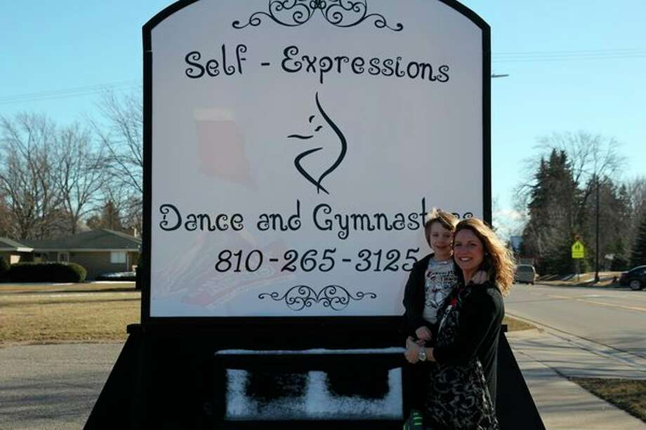 Kim Rathje and her son, Korbin, are pictured in front of the new Self-Expressions Dance and Gymnastics sign located at 524 N. Port Crescent St. in Bad Axe. (Mike Gallagher/Huron Daily Tribune)