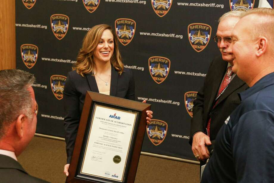 Montgomery County Sheriff's firearms examiner Stephanie Luehr holds the official ANAB accreditation while celebrating with colleagues during the accreditation ceremony for the Montgomery County Sheriff's Office Crime Laboratory's Firearms and Toolmarks section on Friday, March 2, 2018, at the Montgomery County Sheriff's Office Training Academy. Photo: Michael Minasi, Staff Photographer / © 2017 Houston Chronicle