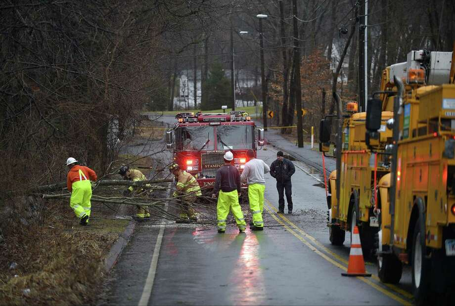 A crew from Eversource Energy and Stamford Firefighters clear away limbs of a fallen tree on Intervale Road on Friday, March 2, 2018 in Stamford, Connecticut. Heavy winds and rain from a powerful Nor'Easter has fallen trees and knock out power to area residents in Southern Connecticut. Photo: Matthew Brown / Hearst Connecticut Media / Stamford Advocate