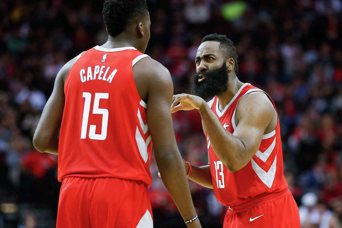 Rockets star James Harden, right, has a few words of advice for center Clint Capela during a break in the action in a game last month against the Mavericks.