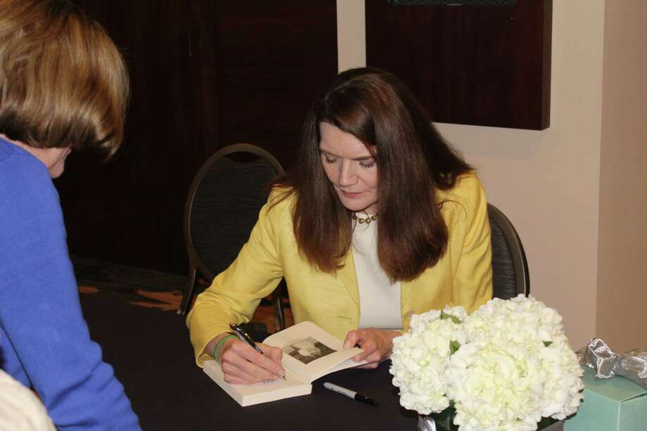 Jeanette Walls, author and guest speaker, signs books and takes photos with fans following the Women Empowering Women Luncheon at The Woodlands Resort on March 2 that helped raise funds for the Interfaith Community Clinic. Photo: Staff Photo By Patricia Dillon