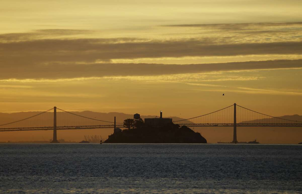 In this photo taken Feb. 1, 2018, Alcatraz Island is seen at sunrise on San Francisco Bay in this view from Sausalito, Calif. In this background is the San Francisco-Oakland Bay Bridge. (AP Photo/Eric Risberg)