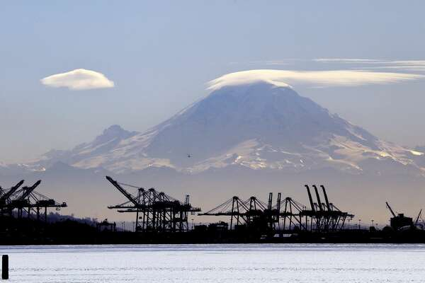 A lenticular cloud, which often signals rainy weather ahead, forms a cap atop Mount Rainier behind cranes that service container ships along the Duwamish River, Tuesday, Feb. 13, 2018, in Seattle.