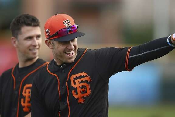 San Francisco Giants' Evan Longoria, right, waves to his daughter in the stands during a spring training baseball practice on Monday, Feb. 19, 2018 in Scottsdale, Ariz. At left is Giants catcher Buster Posey. (AP Photo/Ben Margot)
