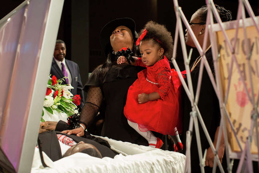Simone McFarlan, holds her daughter, Kaydence Polk, 1, as she grieves over Chris Polk, her best friend of 18 years and Kaydence's father, during the funeral for Polk at Place for Life church in San Antonio on Friday, March 2, 2018. Polk, a local rap artist, was shot and killed at the age of 25 after a perfomance last weekend. McFarlan and Polk met in third grade when she was a cheerleader for his youth football team.