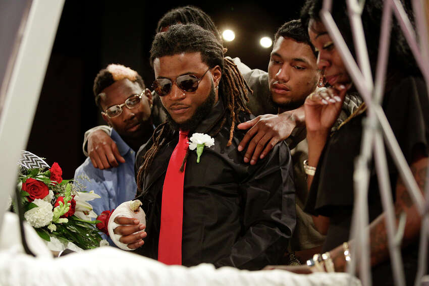 Patrick Hill, center, grieves at the casket of local rapper Chris Polk, with Cederian Lejeune, left, and Nhc Bobo, right, during Polk's funeral at Place for Life church in San Antonio on Friday, March 2, 2018. Hill, Polk's manager, was in the car with Polk when Polk was shot and killed after a performance last weekend. Hill was also shot in the hand.