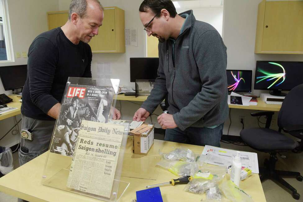 Patrick O'Neill, left, site manager for the Vietnam Veterans Memorial Fund, and Brandon Verdu, a product manager with Creatacor work on assembling some artifacts that have been left at the Vietnam War Memorial in Washington on Thursday, Feb. 22, 2018, in Clifton Park, N.Y. The artifacts will be part of a display in a mobile education center that travels with The Wall That Heals. Employees at Creatacor volunteered their time to fabricate the 75% scale wall replica of the Vietnam War Memorial. This traveling wall will be the largest replica wall out of the four replica walls that are displayed around the United States. This wall, The Wall That Heals, is the only wall that is operated by the Vietnam Veterans Memorial Fund, which is the founding organization of the actual wall in Washington D.C. 58,318 names are on the 144 panels that when erected will stretch 375 feet. The tallest panel is seven feet, eight inches tall. This new replica wall will be unveiled next week in Texas. (Paul Buckowski/Times Union)