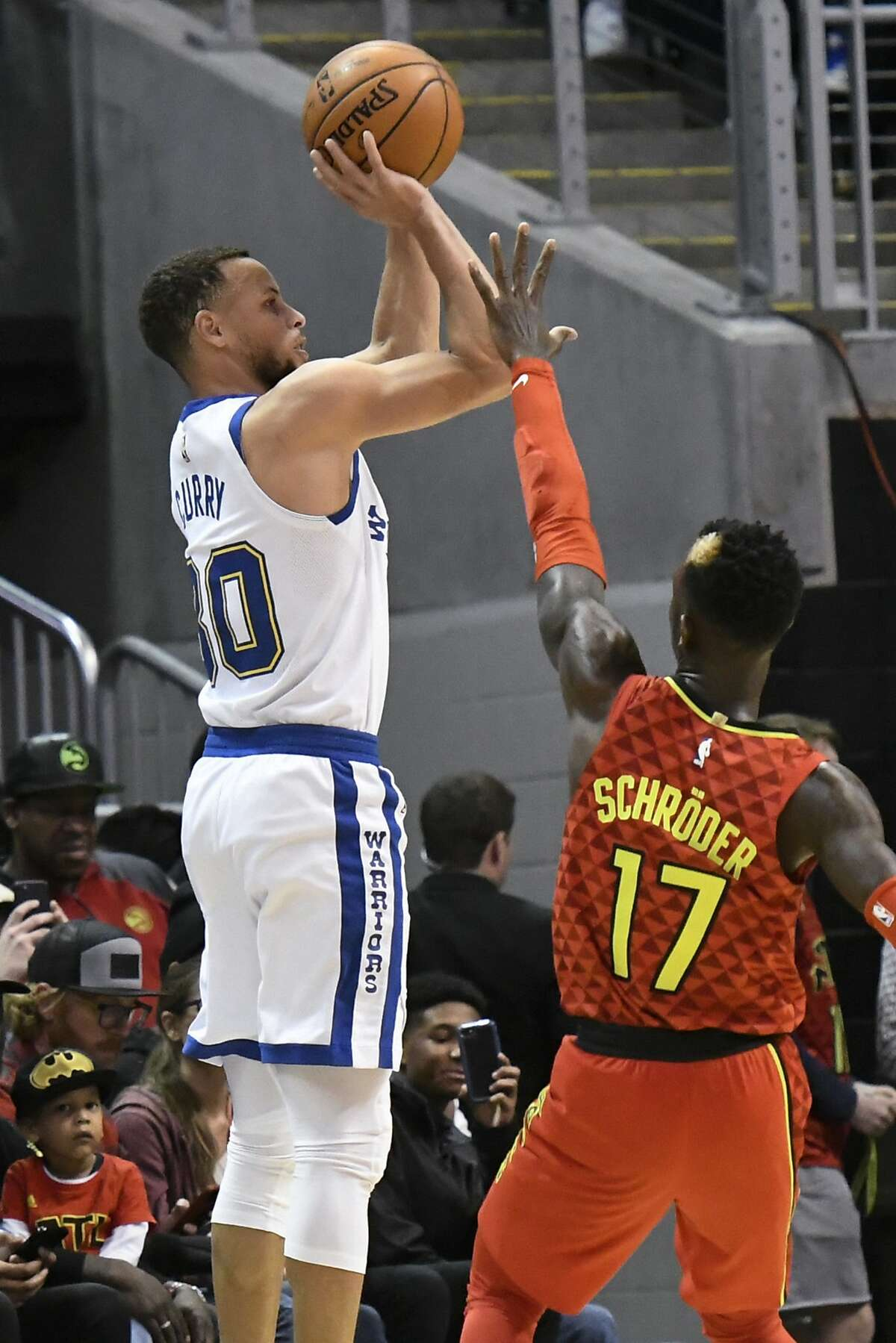 Golden State Warriors guard Stephen Curry shoots from the three-point line as Atlanta Hawks guard Dennis Schroder (17) defends during the first half of an NBA basketball game Friday, March 2, 2018, in Atlanta. (AP Photo/John Amis)