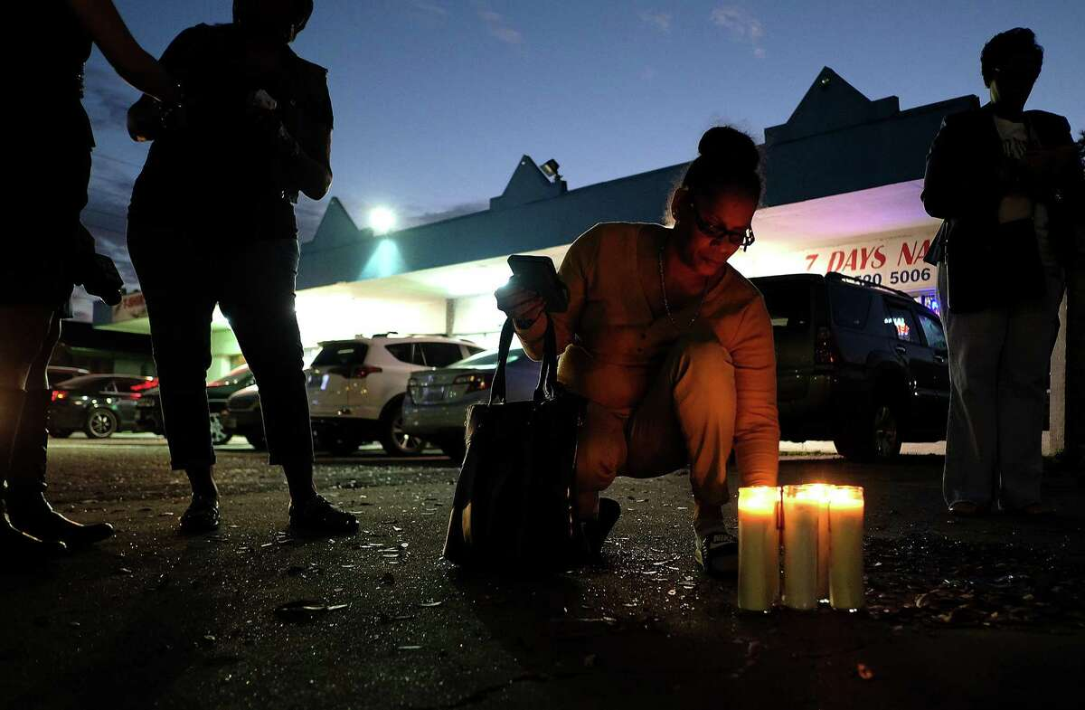 Bridgette Gaston, grandmother to two children who were shot, adjusts the candles she lit in the parking lot where the incident happened on Friday, March 2, 2018, in Houston. ( Elizabeth Conley / Houston Chronicle )