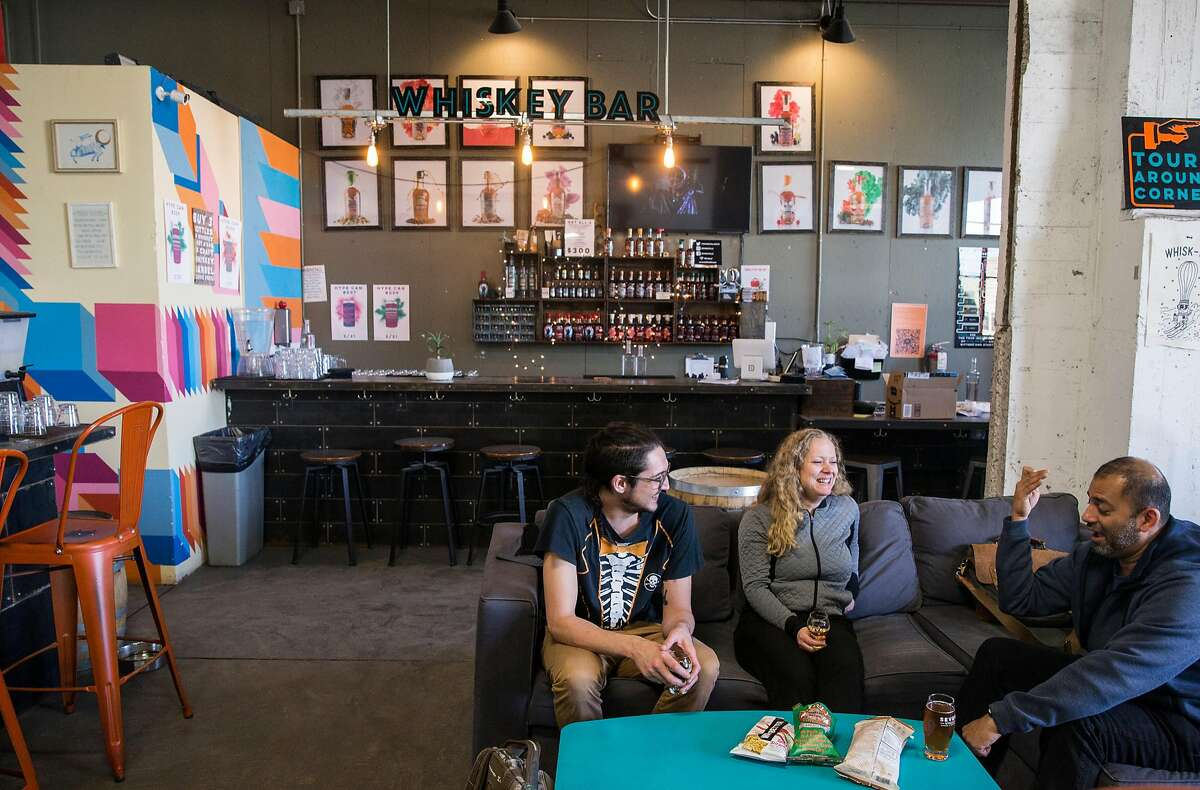 People enjoy beers in the main taproom of Seven Stills Brewery and Distillery Thursday, March 1, 2018 in the Bayview District of San Francisco, Calif.