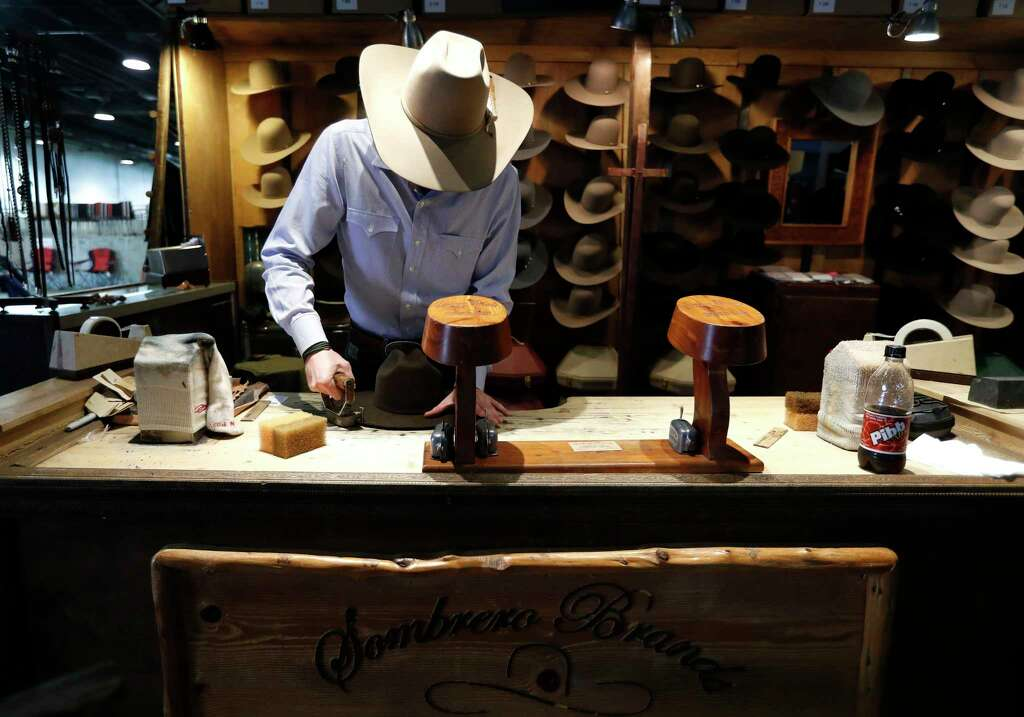 Clay Hand, of Sombrero Brands, shapes a hat in the booth during the Houston