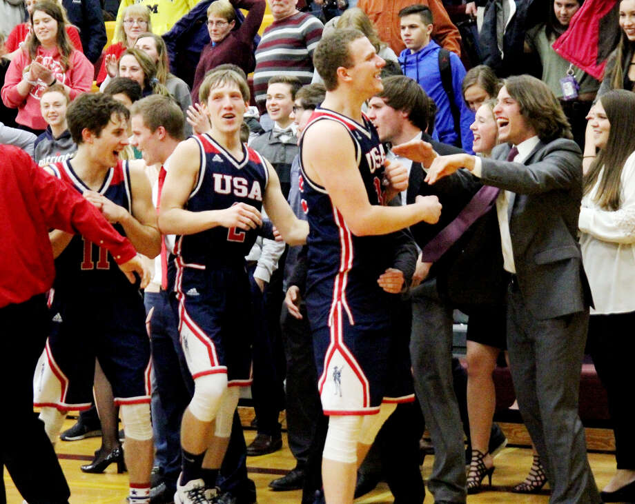 USA players Isaiah Williamson, Tyler Heckroth (2) and Micah Cramer (11) celebrate the team's 69-50 victory over Reese with the fans, Thursday at Reese. The victory completes a perfect 20-0 regular season for the Patriots. (Mike Gallagher/Huron Daily Tribune)