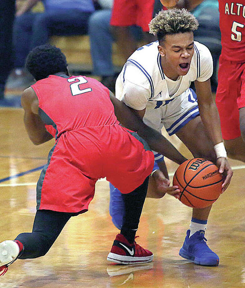Quincy High's Jaeden Smith, right, attempts to steal the ball from Alton's Kevin Caldwell during their Class 4A Regional Championship game Friday in Quincy. Photo: Phil Carlson, Quincy Herald-Whig Photo