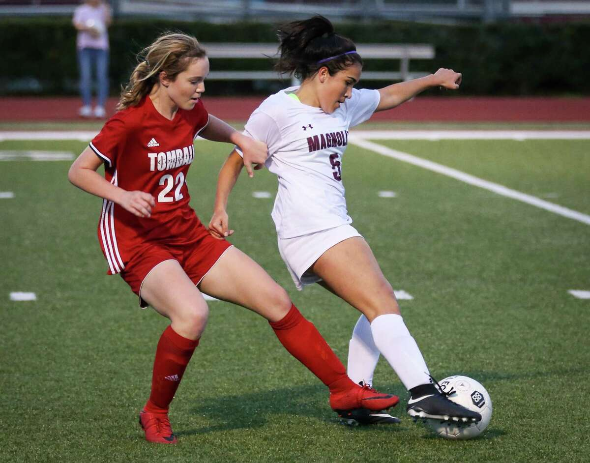 Magnolia's Izzy Cardenas (5) kicks the ball as Tomball's Shelby Willey (22) defends during the girls soccer game on Tuesday, Feb. 27, 2018, at Magnolia High School. (Michael Minasi / Houston Chronicle)
