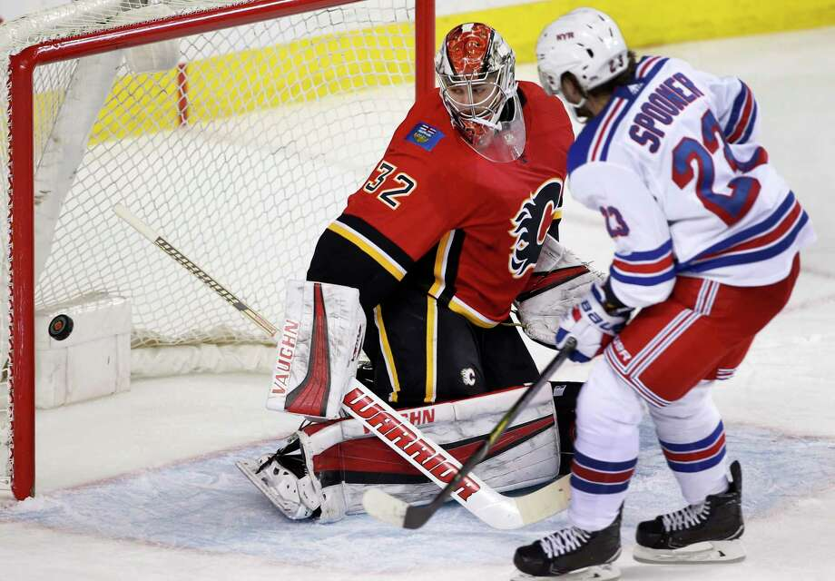 New York Rangers' Ryan Spooner, right, scores against Calgary Flames goalie Jon Gillies during second-period NHL hockey game action in Calgary, Alberta, Friday, March 2, 2018. (Larry MacDougal/The Canadian Press via AP) Photo: Larry MacDougal / The Canadian Press