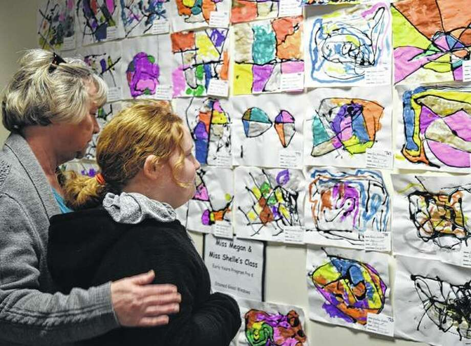 Zoe Prewitt, 8, the daughter of Veronika and Chris Prewitt of Jacksonville, looks at artwork Friday with Linda Prewitt at the Regional Office of Education Art Show at Lincoln Land Community College. Photo: Samantha McDaniel-Ogletree | Journal-Courier