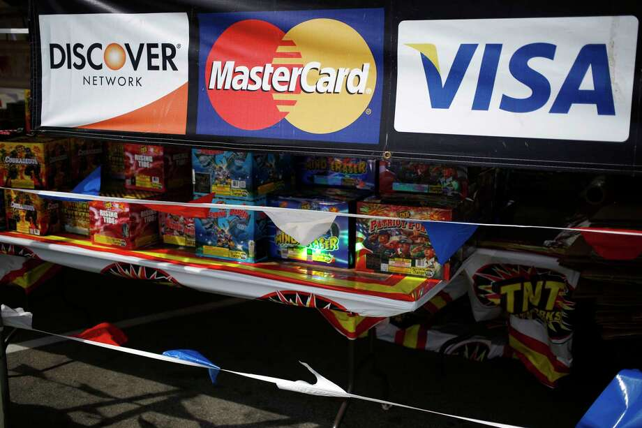 Visa, Mastercard, and Discover Network credit card signage is displayed at a fireworks stand in Shepherdsville, Kentucky, on June 28, 2017. Photo: Bloomberg Photo By Luke Sharrett. / © 2017 Bloomberg Finance LP