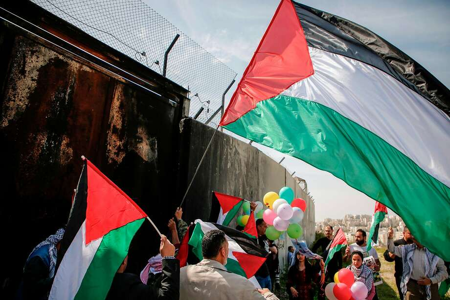 Protesters wave Palestinian flags at the separation wall near the West Bank village of Bilin on Friday. Photo: ABBAS MOMANI, AFP/Getty Images