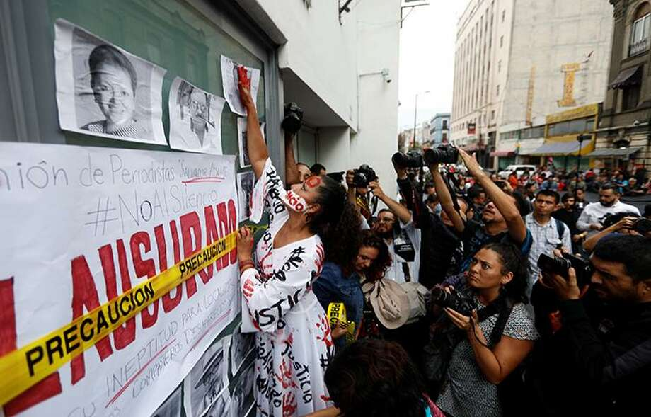An activist puts on a window pictures of journalists who have been killed in Mexico during a demonstration against the murder of journalists in Mexico, outside the building of Attention to Crimes against Freedom of Expression in Mexico City, Mexico, June 15, 2017. Photo: /Committee To Protect Journalists / X01998