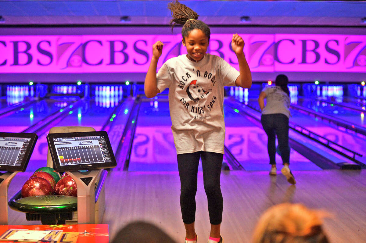 """Amara Odukwu with the Midland Family Care bowling team celebrates after knocking down pins during the Annual Big Brothers Big Sisters """"Bowl for Kids Sake"""" fundraiser March 3, 2018, at Bowlero. James Durbin/Reporter-Telegram"""