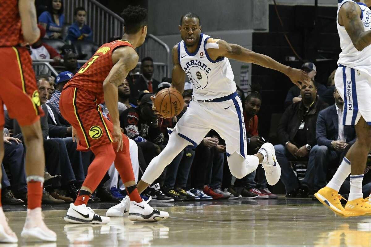 Golden State Warriors forward Andre Iguodala (9) works the flooragainst Atlanta Hawks guard Jaylen Morris, left, during an NBA basketball game Friday, March 2, 2018, in Atlanta. (AP Photo/John Amis)