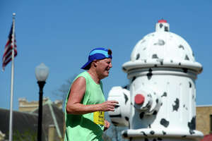 A runner passes the giant fire hydrant in C.A. Shelton Plaza downtown during the Gusher Marathon, Half Marathon and 5K on Saturday.  Photo taken Saturday 3/3/18 Ryan Pelham/The Enterprise