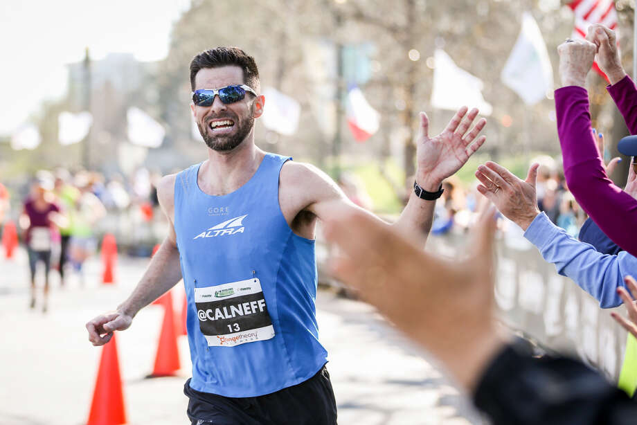 Calum Neff, of Katy, slaps hands with spectators as he approaches the finish line in first place for men's overall during the 6th annual The Woodlands Marathon on Saturday, March 3, 2018, in The Woodlands. (Michael Minasi / The Courier)