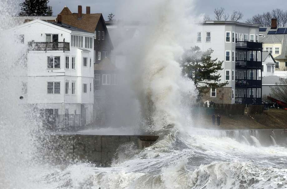 A wave crashes into a seawall in Winthrop, Mass. The storm swept in Friday, causing more than 2,800 flight cancellations, mostly in the Northeast, and disrupting passenger train service. Photo: Michael Dwyer, Associated Press