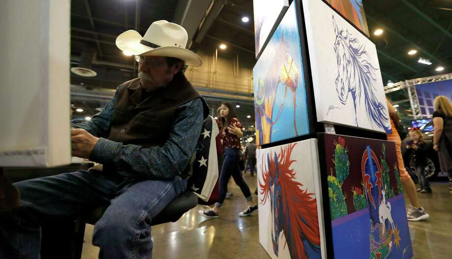 Lyndon Gaither paints in his booth, as he sells his colorful western-themed paintings at the Houston Livestock Show and Rodeo at NRG Center, Saturday, March 3, 2018, in Houston. Photo: Karen Warren, Houston Chronicle / © 2018 Houston Chronicle