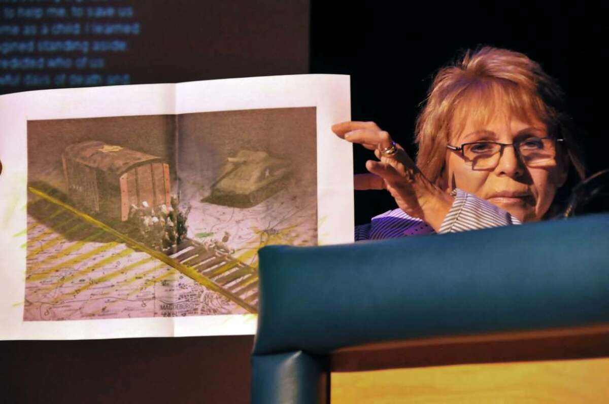 Holocaust survivor Sara Atzmon of Israel displays a painting she made to commemorate the liberation by American soldiers of the concentration camp train she was being transported in at the end of WWII during the Holocaust Survivors Reunion three-day symposium at Hudson Falls High School. (John Carl D'Annibale / Times Union)