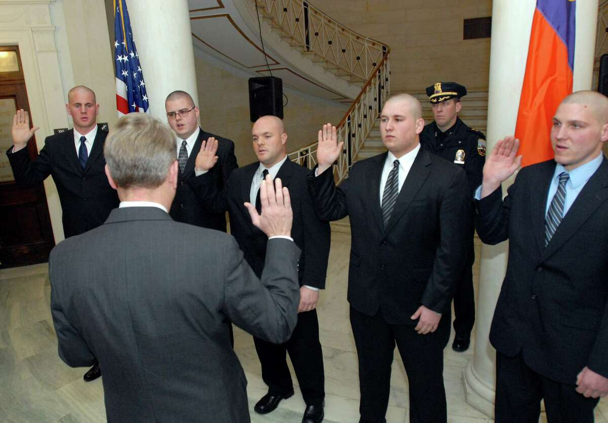 Mayor Brian Stratton, center, swears in five police recruits during a ceremony on Tuesday, Jan. 19, 2010, at City Hall in Schenectady, N.Y. The recruits, from left, are Andrew MacDonald, Brandon Shepler, Robert Young Jr., Douglas Smith and Christopher Wilgocki. (Cindy Schultz / Times Union)